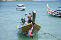 Tajlandzki mężczyzna sprawdza drewniany rybołówstwo łodzi unosić się i naprawia Obraz Royalty Free