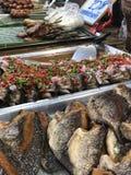 Tajlandzki noc rynek z krajowym jedzeniem: smażąca ryba, suszi, ryżowi cukierki, skewers, suszi, owoce morza obraz royalty free