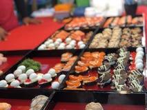 Tajlandzki noc rynek z krajowym jedzeniem: smażąca ryba, suszi, ryżowi cukierki, skewers, suszi, owoce morza fotografia royalty free