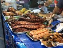 Tajlandzki noc rynek z krajowym jedzeniem: smażąca ryba, suszi, ryżowi cukierki, skewers, suszi, owoce morza zdjęcia stock