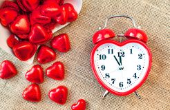 Tajma för förälskelse Röd hjärta formad klocka med söta choklader Royaltyfri Foto