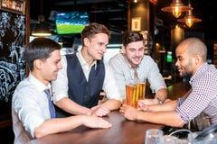 Tajma för att dricka öl Fyra vänner som dricker öl och har gyckel till Royaltyfri Fotografi