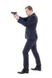 Tajnego agenta mężczyzna w garniturze pozuje z pistoletem odizolowywającym na wh Zdjęcie Royalty Free