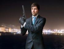 Tajny agent lub zabójca trzymamy krócicę z silencer w rękach przy nocą Obraz Royalty Free