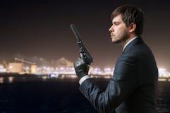 Tajny agent trzyma krócicę z silencer w ręce przy nocą Obrazy Royalty Free
