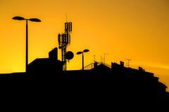 Tak av byggnader med många antenner i en storstad på solnedgången Arkivbild