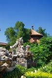 Tak av den kinesiska pagoden i frodig grön trädgård med rockeryen och trädet royaltyfri bild