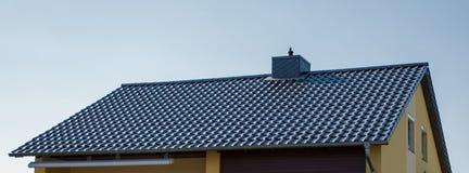 Tak av ett hus med svarta tegelplattor royaltyfri foto