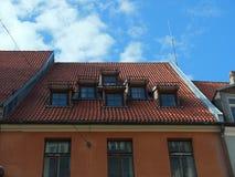 Tak för röd tegelplatta med vindskupor Arkivbild