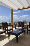 Tak framme av havet med brunbrända sängar, armchais, blå himmel och vitmoln Royaltyfria Bilder