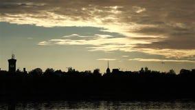 Tak och maxima av forntida slottar och hus ovanför vattnet på solnedgånghimmel lager videofilmer