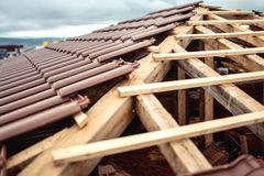 Tak under konstruktion med buntar av brunt, moderna tegelplattor som täcker huset Royaltyfri Foto