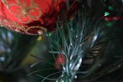 Tak van een kunstmatige die Kerstboom, met een leuke rode bal wordt verfraaid stock afbeeldingen