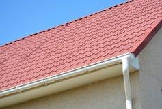 Takavloppsränna med taket för röd metall för hus det belade med tegel royaltyfri fotografi