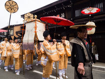 Takayama Autumn Festival parade on town streets. Takayama, Japan - October 10, 2015: Local men in traditional costumes carrying a portable shrine along the Stock Photography