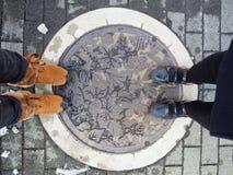 TAKAYAMA, JAPAN - February 15, 2017: Shoe of friends  stand on manhole cover of Takayama city. Top view. Royalty Free Stock Photography