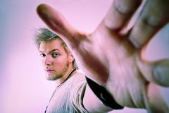 Take that !. Nervous male in aggressive stance with outstretched hand at reach of camera Stock Image