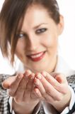 Take this. Young attractive businesswoman with open palms toward camera - add your item - focus on the hands royalty free stock images