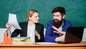 Take into account educational norms. Prepare for school lesson. Teacher and supervisor working in school classroom. School educator with laptop and principal royalty free stock images