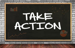 TAKE ACTION. On brick wall and chalkboard background Royalty Free Stock Images
