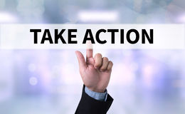 TAKE ACTION. Business man with hand pressing a button on blurred abstract background Stock Photography