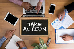 TAKE ACTION. Business team hands at work with financial reports and a laptop, top view Royalty Free Stock Image