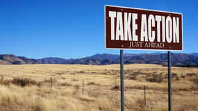 Take Action Just Ahead brown road sign Stock Photo