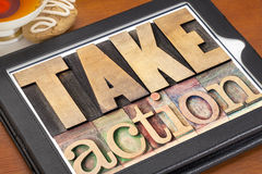 Take action motivation. Take action - motivation concept - text in vintage letterpress wood type on a digital tablet royalty free stock images