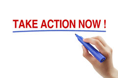 Take Action Now. Hand with blue marker is drawing a line under the text Take Action Now isolated on white background stock images