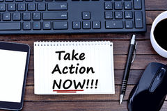 Take action Now words on notebook Stock Image