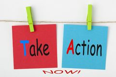 Take Action Now. Written on color notes with wooden pinch on white background. Business Concept stock photo