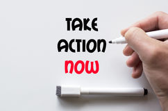 Take action now written on whiteboard. Human hand writing take action now on whiteboard Stock Photography