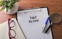 Take Action word on paper with glass ballpen and green plant. Take Action word on paper with glass ballpen and green plant Stock Image