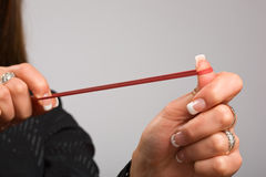 Take aim with rubber band. Woman's hands firing rubber band Royalty Free Stock Photo