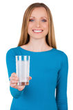 Take aspirin!. Young woman holding a glass with water and aspirin in it while standing isolated on white Stock Image