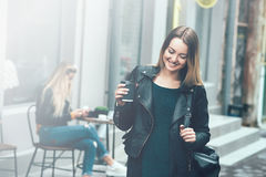 Take away coffee. Beautiful young urban woman wearing in black stylish clothes holding coffee cup and smiling while walking along Royalty Free Stock Photo