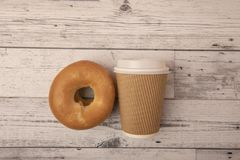Take away coffee cup with bagel. On wooden background stock images