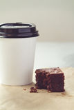 Take away coffee cup and chocolate brownie in muted tones Stock Photos