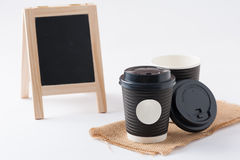 Take away coffee cup. Take away paper coffee cup with white sticker label for logo, text or message and small A-frame black board in blurry background Royalty Free Stock Photos