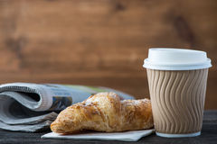 Take away coffee and fresh croissant and newspaper. On wooden background Royalty Free Stock Photos