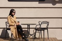 Free Take Away Coffee In Women`s Hands. Beautiful Young Brunette Woman Wearing Brown Coat Sitting At Table In Street Outdoor Cafe And Stock Photography - 144090192