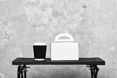 Take away coffee and white package on table. stock images