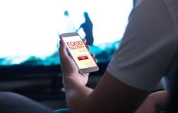 Take away food order online with delivery app and smartphone. Man buying pizza or fast food home while watching TV stock photography