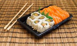 Take away mixed sushi dish with chopsticks Royalty Free Stock Photos