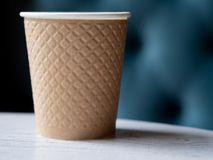 Take away a plastic cup of coffee on a wooden table. Take away a plastic cup of coffee on a wooden table with a blurred background with space for text or royalty free stock photo