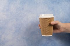Take away recyclable paper and plastic coffee cup on a blue background. With copyspace royalty free stock image