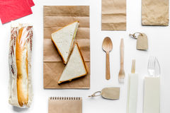 Take away with sandwich and paper bags on table background top view Stock Photos