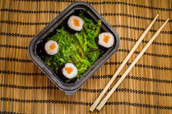 Take away sushi dish with algae and chopsticks Royalty Free Stock Photos