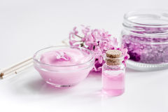 Take bath with lilac cosmetic set and blossom on white table background Stock Images