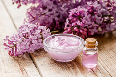 Take bath with lilac cosmetic set and blossom on wooden table background Royalty Free Stock Images